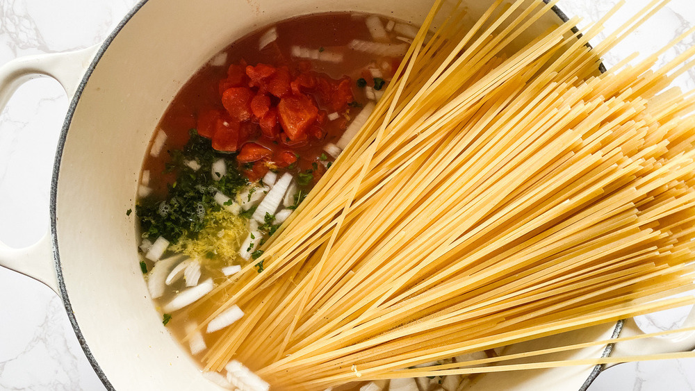 Pasta and ingredients in broth in Dutch oven