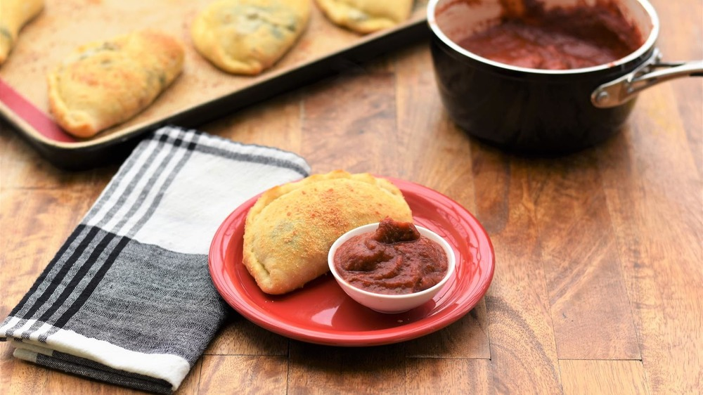 Calzone on a plate with dipping sauce