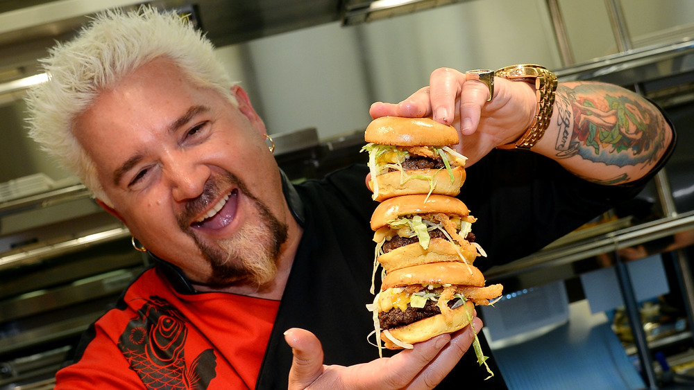 Guy Fieri holds stack of burgers