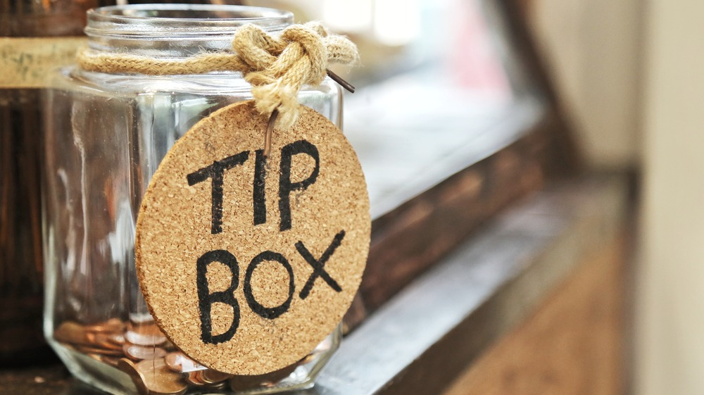 Glass tip jar on wooden counter